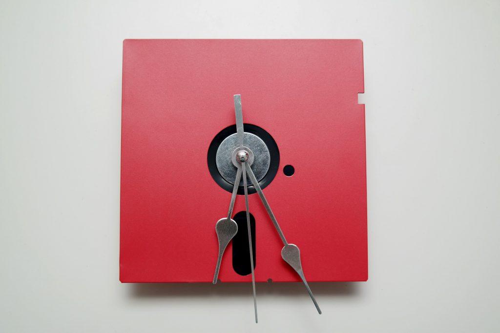 Rote 5,25-Zoll Diskette mit eleganten, silbernen Zeigern.