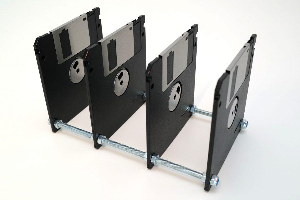 Schwarze 3,5-Zoll Disketten, aufgereiht auf Gewindestangen.