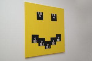 Schwarze Disketten auf gelber Leinwand, Smilie